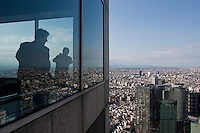 Tourists look out at Shinjuku skyscrapers from the 45th floor observation deck of the Tokyo Metropolitan Government building. Saturday, November 28th 2009