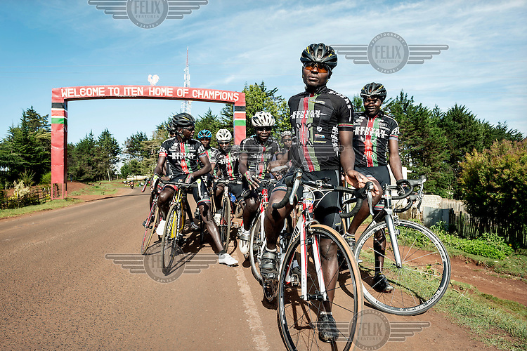 The Kenyan Riders, a Kenyan cycling team, gather before an arch over the road at the entrance of Iten with a slogan welcoming visitors to the 'home of champions'. The team train along the road between Eldoret and Iten, a small town in the highlands on the edge of the Great Rift Valley at an altitude of 2400 metres, a perfect location for high altitude training. The team is managed by Singaporean Nicholas Leong and trained by Australian Simon Blake.