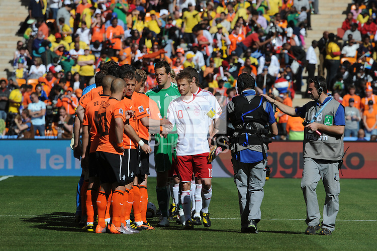 Danish and Dutch players exchange greetings following the national anthems, as the hand-held Steadi-Cam covers for the television feed. Holland defeated Denmark, 2-0, June 14th, at Soccer City in the opening match of Group E of the 2010 FIFA World Cup.