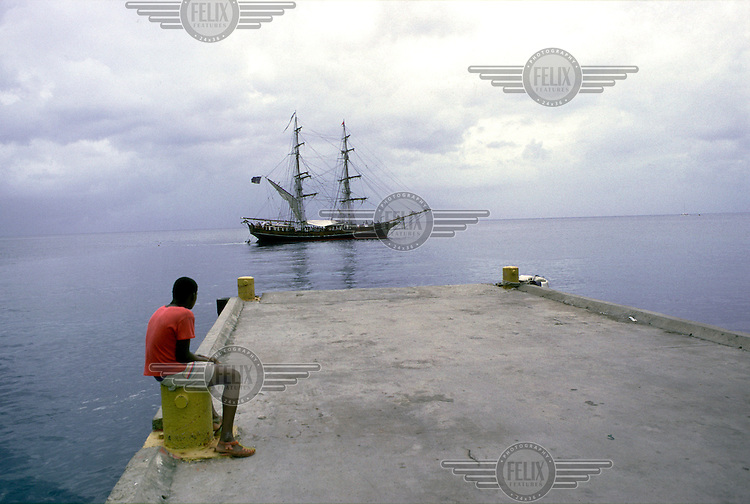 A teenager watches as a tourist cruiser leaves port.