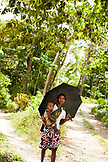 PHILIPPINES, Palawan, Barangay region, a woman and her baby take shade under an umbrella in the small village Purok Tarabidan