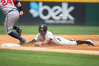 Leury Garcia (24) of the Charlotte Knights slides head first into third base during the game against the Gwinnett Braves at BB&T BallPark on May 22, 2016 in Charlotte, North Carolina.  The Knights defeated the Braves 9-8 in 11 innings.  (Brian Westerholt/Four Seam Images)
