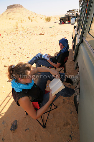 Africa, Tunisia, Tembaine. Tourists resting in the shade of their Land Rover. --- No releases available, but releases may not be needed for certain uses.