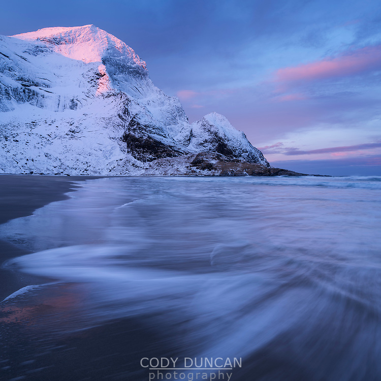 Winter sunrise over snow covered mountain peaks rising above Bunes beach, Moskenesøy, Lofoten Islands, Norway