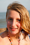 Full face portrait smiling young teenage blonde girl at seaside