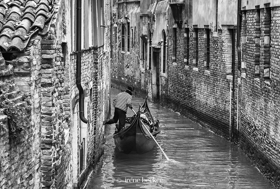 A gondola being steered through the narrow canals in Venice, Italy