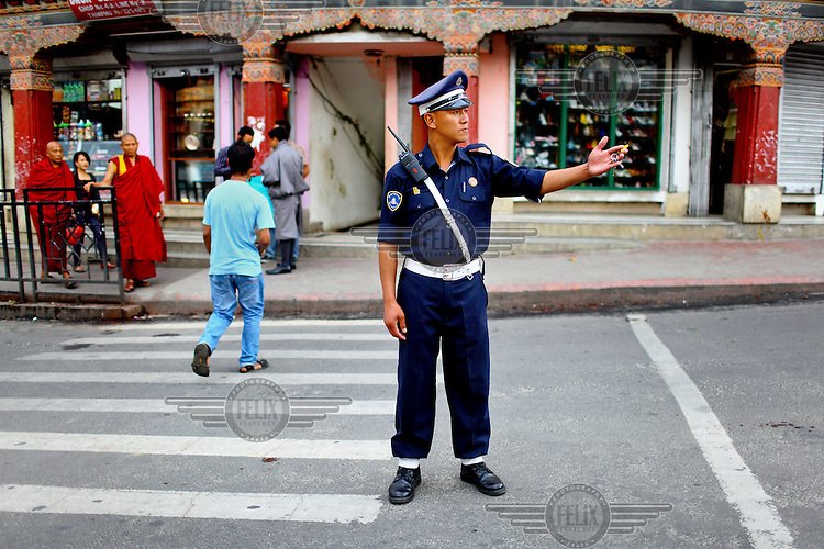 A traffic policeman directs traffic at a crossing on a street in Thimpu.