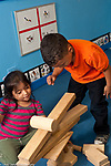 Education preschool 3-4 year olds boy and girl working together building block structure, watching cylinder block roll down incline they made