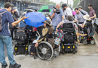 "Members of the Taxis For All Campaign and their supporters protest in the rain in front of Uber headquarters in West Chelsea in New York on Thursday, July 30, 2015. The protesters had a ""roll-in"" calling on the company to stop discriminating against the disabled by requiring handicapped accessible vehicles. Out of 20,777 Uber cars on the road not one of them is wheelchair accessible. (© Richard B. Levine)"