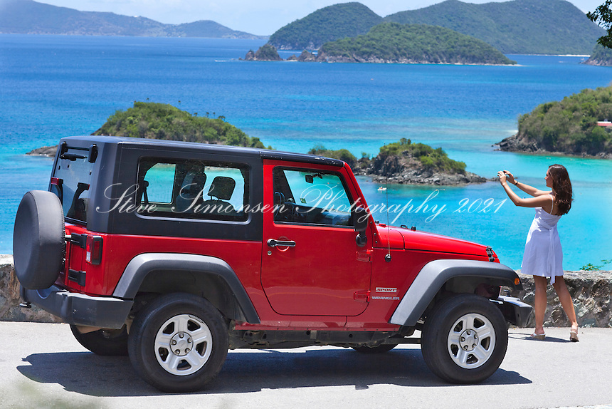 Tourist taking a picture near a red jeep<br />