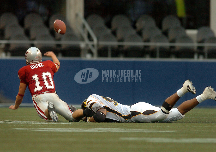 Sep 17, 2005; Seattle, WA, USA; Washington State Cougars quarterback Alex Brink #10 throws the ball as he is tackled by Grambling State Tigers defensive end Jason Hatcher #90 in the third quarter at Qwest Field. Mandatory Credit: Photo By Mark J. Rebilas