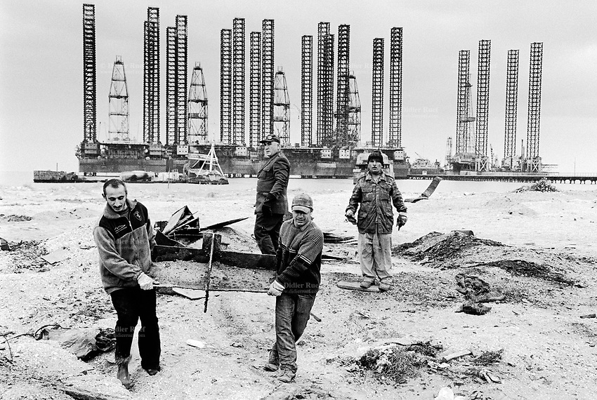 """Azerbaijan. Baku Region. Chikhov is 15 km from Baku. A group of men, all manual workers, carry heavy metals parts in order to be recycled and sold as scrap iron. Scrapheap. State Oil Company of Azerbaijan Republic (SOCAR) is the project owner of the drilling derricks and """"Jack Up"""" rigs used as oil-extracting infrastructure. Caspian sea.  © 2007 Didier Ruef"""