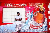 Man standing in front of Red Stripe beer ad. Robert. Jamaica Tourism.