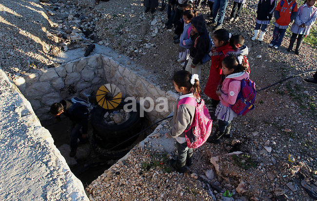 Palestinian students walk through a sewage tunnel to get to school near the West Bank village of Jaba' , southern Jinin, on Feb. 05, 2013. Students try to avoid cross the main road traffic which caused many accidents and killed students. Photo by Issam Rimawi