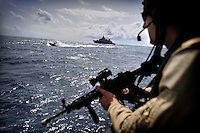 Dutch battleship Hr Ms Evertsen can be seen in the background as a member of the Dutch Special Forces stands guard aboard the Fade I cargo ship, a WFP (World Food Programme) vessel delivering 5,000 tonnes of food aid to Somalia. Many aid ships have been hijacked by pirates in these waters, and the Dutch Navy monitor the vessels to try and prevent further attacks.