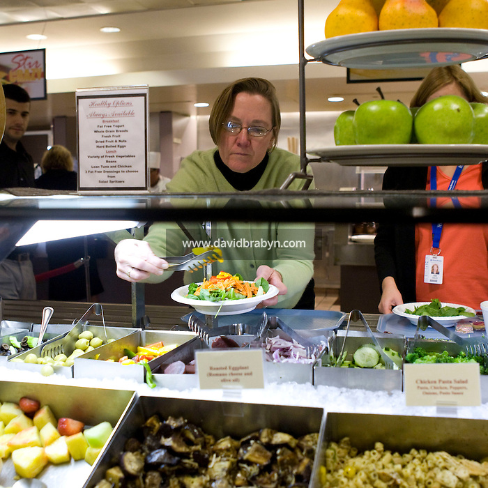 Maureen Fahy picks food from the salad bar in the cafeteria at the Pitney Bowes headquarters in Stamford, CT, United States, 7 October 2008.