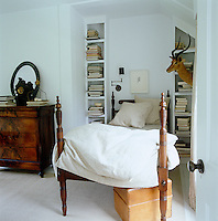 In a guest bedroom the antique bed is situated between two tall bookshelves crammed with books