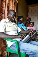 UGANDA, Arua, village Onduparaka, man and family listen radio