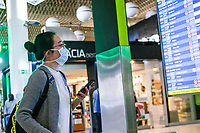 LISBON, PORTUGAL - March 11:  A passenger wearing a protective mask checks a electronic board in the airport on March 11, 2020 in Lisbon, Portugal. <br /> The International Air Transport Association (IATA) warned earlier on Thursday that the virus could rob passenger airlines of up to $113 billion in revenue this year as fears of a pandemic that could plunge the global economy into recession grow.<br /> Airlines across the globe are rushing to cut flights and costs, and warning of a hit to earnings.<br /> Portugal, whose economy depends heavily on tourism, has so far reported 59 positive cases of the Coronavirus, far fewer than the more than 2200 cases in neighboring Spain.<br />  <br /> (Photo by Luis Boza/VIEWpress vía Getty Images)