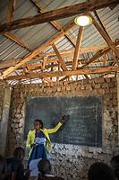 Uganda, Mmanze. Solar lights used in classrroms at Christ City School. Olive Nakiremue, headmaster is teaching.