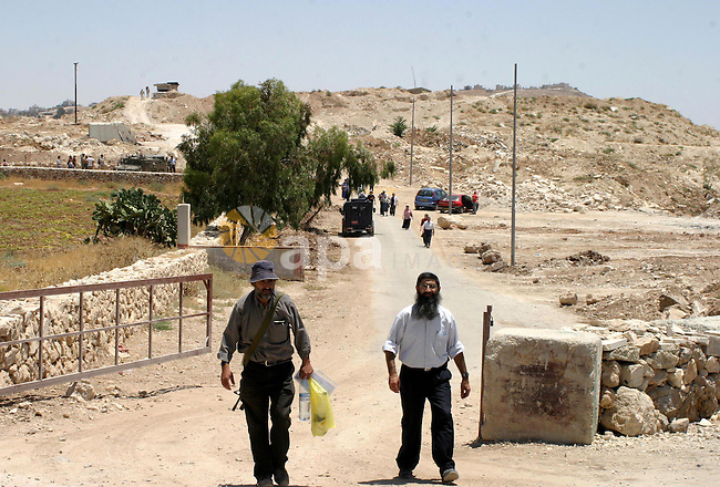 Israeli settlers walk in an evacuated Israeli military camp on the edge of Beit Sahour town near the West Bank city of Bethlehem.  Around 60 Israeli settlers gathered on Thursday in Shdema, the previous name of an area of an evacuated Israeli camp, in Osh Ghrab area.