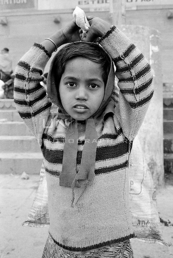 A working kid, carrying wood to be sold for funeral pyres.<br /> India, 2012