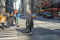 A shopper on Fifth Avenue in Midtown Manhattan in New York on Sunday, November 27, 2016. The National Retail Federation reported that 43.8% of consumers shopped online during the four-day weekend.  (© Richard B. Levine)