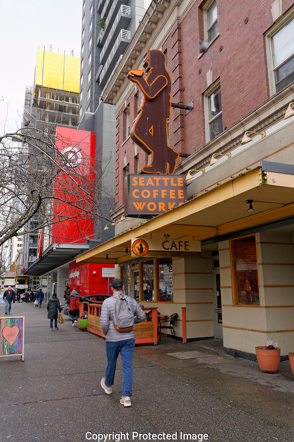 Man walking past the Seattle Coffee Works coffee shop sign  in downtown Seattle, Washington, USA