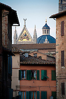Gold mosaic on facade of the Cathedral of Siena, Duomo di Siena, tower above a row of tuscan style houses with green shutters, Siena, Tuscany, Italy