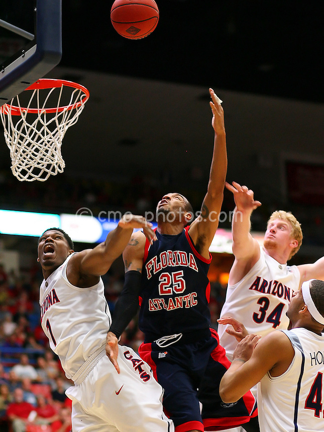 Nov 17, 2008; Tucson, AZ, USA; Florida Atlantic Owls guard Paul Graham III (25) attempts a shot between Arizona Wildcats forward Fendi Onobun (1) and forward Chase Budinger (34) in the first half of a NIT Season Tip-Off game at the McKale Center.  Arizona won the game 75-62.  Mandatory Credit: Chris Morrison-US PRESSWIRE