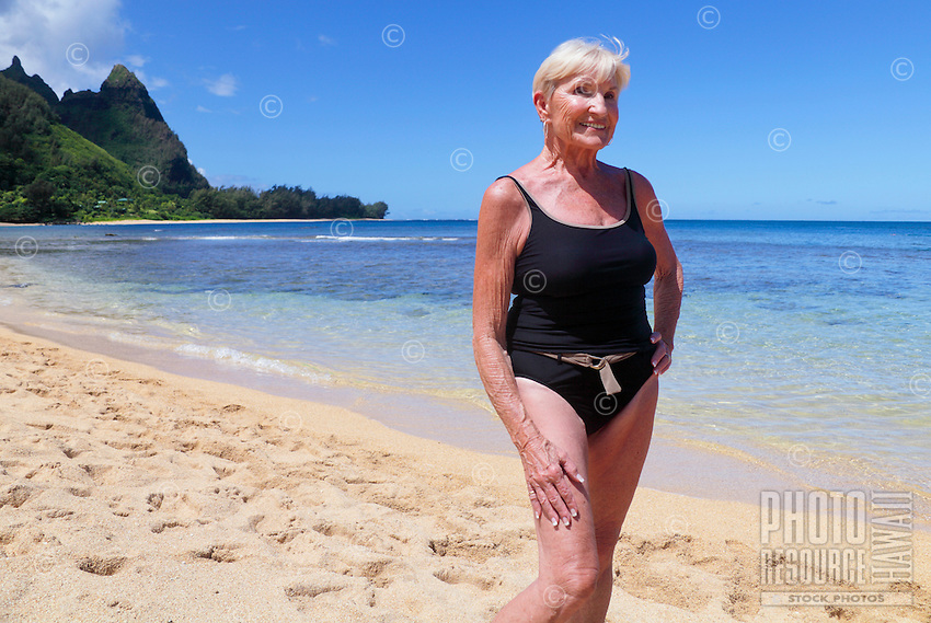 A senior citizen enjoys the day at Tunnels Beach, with Makana Mountain (or Bali Hai) in the distance, northern Kaua'i.
