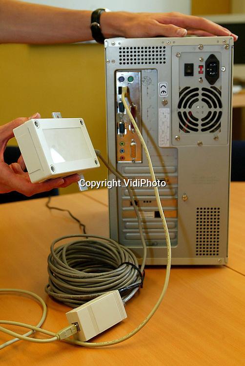 Foto: VidiPhoto..GENDT - Technicus Tom Tijssen demonstreert hij eenvoudig het is een draadloze internetverbinding te installeren.