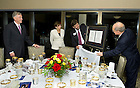 September 29, 2011; Professors James McAdams and Vittorio Hosle (right) unveil a gift for Dr. Horst Koehler, former President of the Federal Republic of Germany and wife, Eva Luise Koehler after dinner in the 14th floor penthouse of the Hesburgh Library. Photo by Barbara Johnston/University of Notre Dame