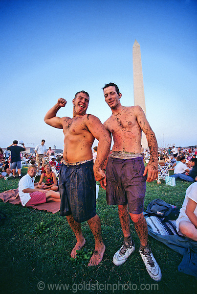 Two young men celebrating 4th of July on the Mall in Washington DC, 1993. They had been playing some kind of game where they rolled around on the ground. So they are shirtless and covered in grass and sweat. Model released from the two principal men only.