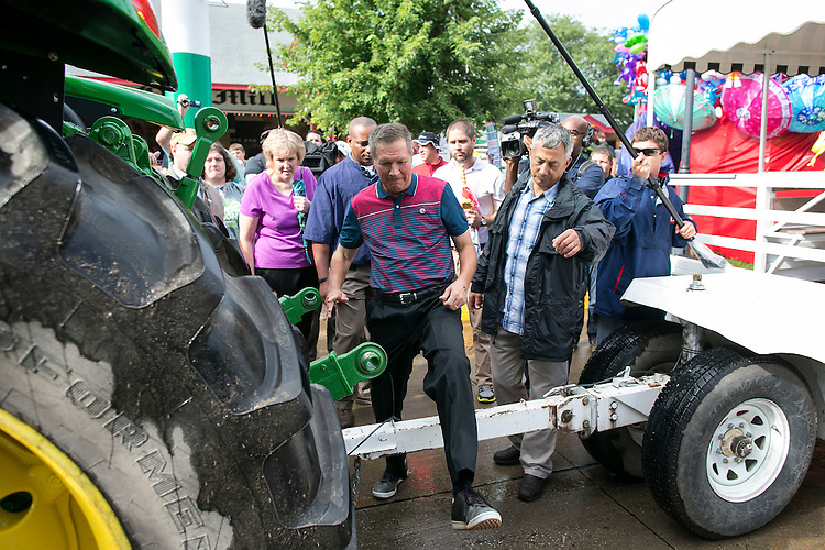 UNITED STATES - August 17: Republican presidential candidate and Ohio Governor John Kasich crosses over a trailer hitch as he prepares to ride a John Deere tractor down the concourse at the Iowa State Fair on Tuesday, August 18, 2015 in Des Moines, Iowa. (Photo By Al Drago/CQ Roll Call)