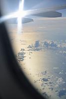 Wings of flying airplane over ocean
