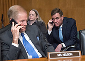 United States Senators Bill Nelson (Democrat of Florida), left, and Mark Warner (Democrat of Virginia), right, speak on their cell phones prior to US Secretary of the Treasury Steven Mnuchin giving testimony before the United States Senate Committee on Finance on the President's Fiscal Year 2019 budget on Capitol Hill in Washington, DC on Wednesday, February 14, 2018.<br /> Credit: Ron Sachs / CNP