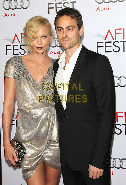 "CHARLIZE THERON & STUART TOWNSEND .arriving at AFI Fest's Gala Screening of ""The Road"" at Grauman's Chinese Theatre in Hollywood, California.  November 4th 2009..half length dress wrap shiny metallic lame gold silver grey gray beaded neckline twenties clutch bag black suit white shirt couple  .CAP/RKE/DVS.©DVS/RockinExposures/Capital Pictures."