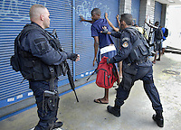 Policemen check suspects at Complexo da Penha, Rio de Janeiro, Brazil, November 25, 2010. Authorities in Rio de Janeiro try to control a fourth day of violence apparently orchestrated by drug gang members who have attacked police stations and burned cars in Rio de Janeiro city as protest by traffickers after being forced from their turf by police occupations of more than a dozen slums in the past two years..(Austral Foto/Renzo Gostoli)
