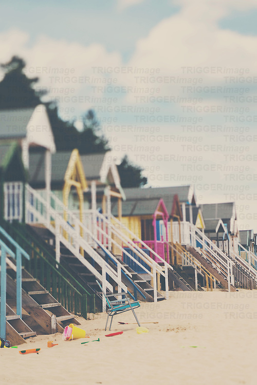 an empty beach chair in front of a row of beach huts in Norfolk, England