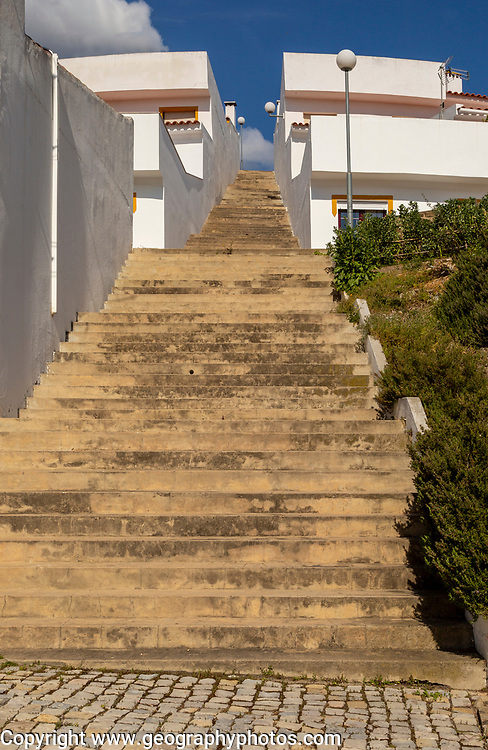 Diminishing converging lines, perspective flight of concrete steps outdoors climbing between two modern whitewashed houses