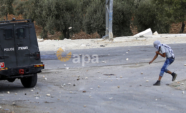 A Palestinian protester throws stones at Israeli security forces during clashes in the West Bank village of Tuqua, south-east of Bethlehem, on October 8, 2015. New violence rocked Israel and the Israeli occupied West Bank, including an incident in which men thought to be undercover Israeli police opened fire on Palestinian stone throwers they had infiltrated, wounding three of them. Photo by Muhesen Amren