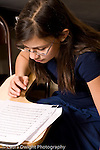 Elementary school Grade 5 arts enrichment female student singing notes from paper she holds wearing glasses vertical