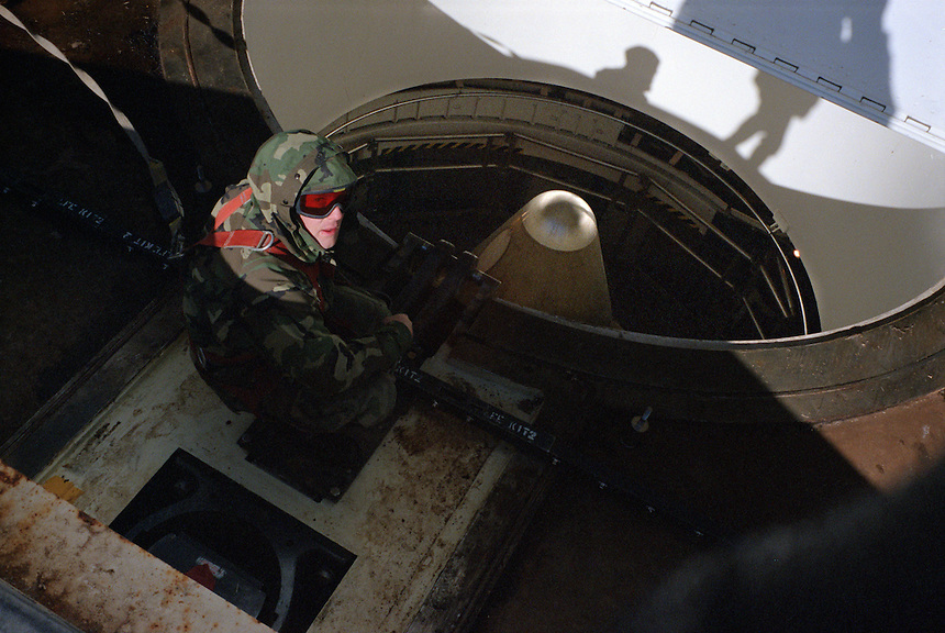 A U.S. Air Force technician looks over the nose cone of a Peacekeeper Intercontinental Ballistic Missile at an open silo in Eastern Wyoming. A battery was being changed after it's ten-year life had run its course. Intense maintenance schedules are performed on the U.S. missile fleet to keep it in a state of readiness despite the end of the cold war. The 80 foot-tall, 196,000-pound missile fits in a cylinder like a piston, allowing crews to gently raise and lower it with only 30 pounds per square inch of air pressure. The missile was raised a few feet to allow access to bolts.