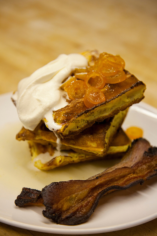 Brunch at Simpatica, a catering company that offers dinner on Friday and Saturday nights, plus a Sunday Brunch.  Located in SE Portland, Oregon. Waffles with kumquat syrup, bacon and creme chantilly.