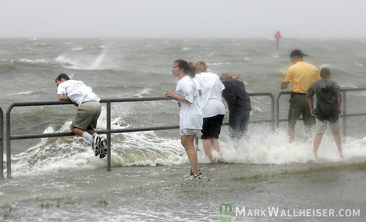 """Thrill seakers along the seawall in Pensacola as the 50 mph plus winds and surf from approaching Hurricane Ivan at Wayside Park in Pensacola September 15, 2004. """"This is awsome"""" said one of those, from Webb City, MO."""