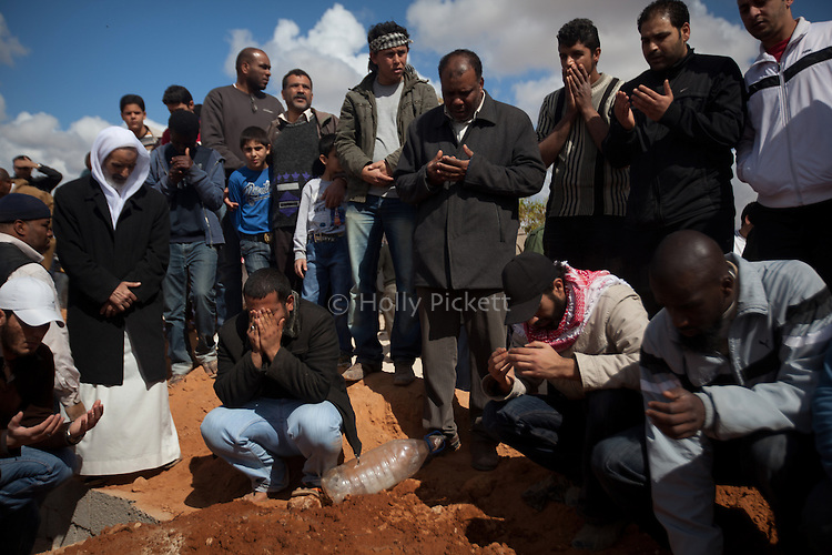 Family and friends pray over a fresh grave during a mass funeral for 20 people, killed during fighting between opposition rebels and loyalist forces of Col. Muammar Qaddafi, in Benghazi, Libya, March 20, 2011. The main hospital in Benghazi reported around 50 dead fighters and civilians the previous day and at least 35 on Sunday.