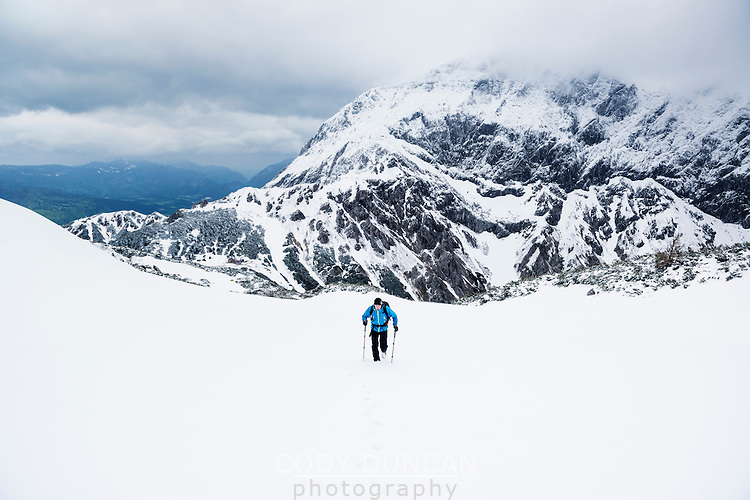 Hiker in winter conditions acending from Torrener Joch pass towards summit of Schneibstein (2276 m),  Hagengebirge, Berchtesgaden Alps, Germany - Austria