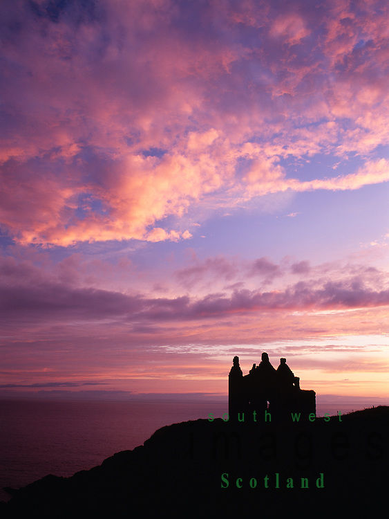 High  on the sea cliffs Dunskey Castle silhouetted against the sunset looking up the North Channel to Ireland near Portpatrick Galloway Scotland UK