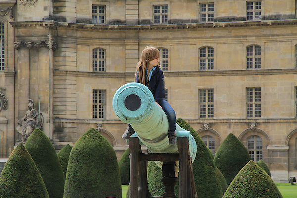 Girl sitting on canon in front of Hotel des Invalides, Paris, France.